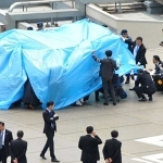 Police and security officers investigate an unidentified drone (under a blue cover) which was found on the rooftop of Prime Minister Shinzo Abe's official residence in Tokyo, in this photo taken by Kyodo April 22, 2015.
