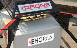 Drone Delivery Canada Drone Carrying a SHOP.CA Parcel