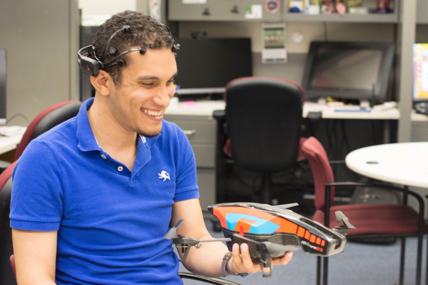 Marvin Andujar, UF human-centered computing doctoral student, and member of our Neurogadget team, poses for a photo with a mind-controlled drone that he programmed with Chris Crawford.