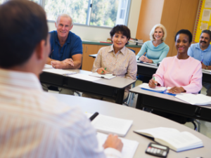 Mature students and their teacher in a classroom, Credit: Stock Image