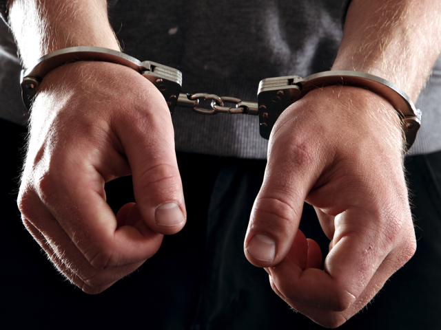 Offender with his hands in handcuffs, Credit: Stock Image