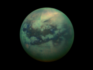 A false-color view of Titan, a moon of Saturn surrounded by a thick orange haze. Titan is believed to contain an ocean with an icy crust on top, which will be simulated in future research., Credit: NASA